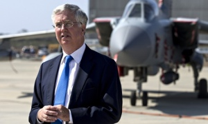 Defence secretary Michael Fallon standing beside an RAF plane